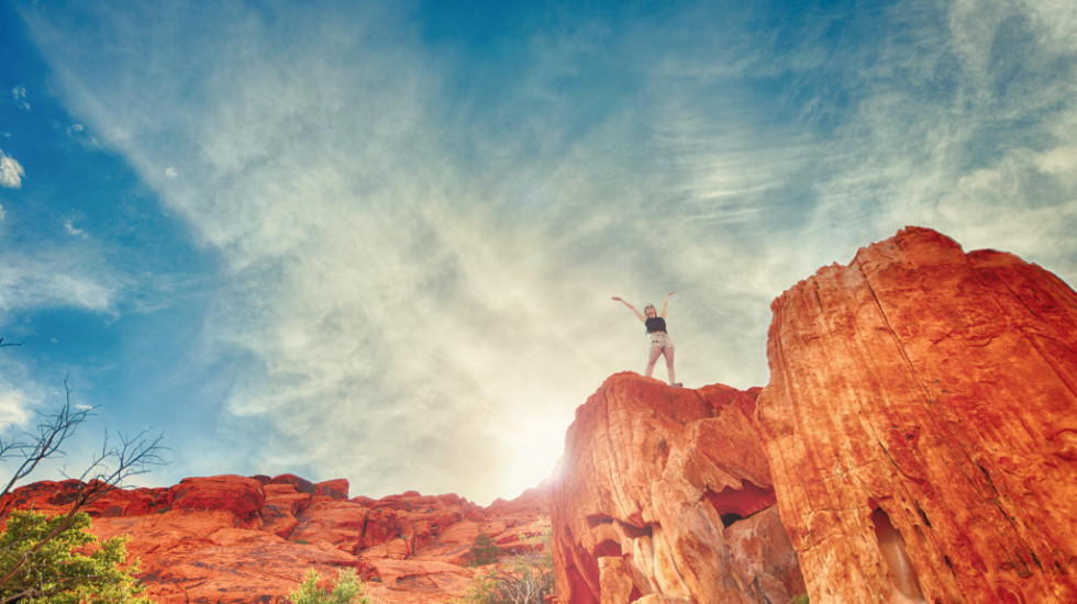 Woman-Standing-On-Red-Rocks-Celebrating-Success-1024x682